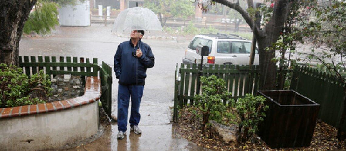איש עומד בגשם בפתח ביתו